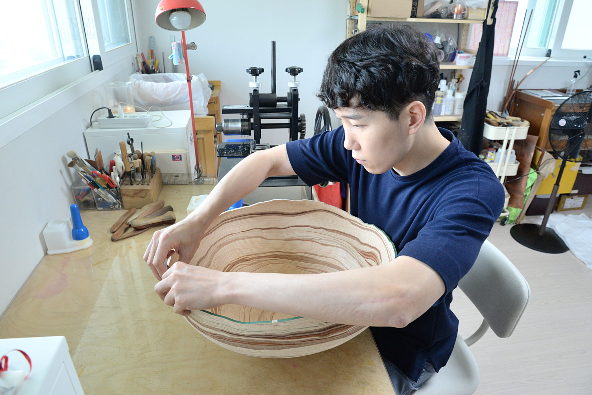 Junsu Kim dans son atelier, posant les lanières de cuir