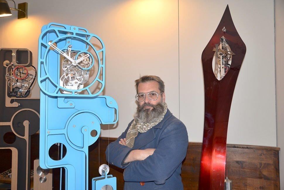 Philippe Lebru, initiateur du renouveau de l'horloge comtoise, et son horloge Pop Up bleue entre sculpture cubiste et robot primitif.