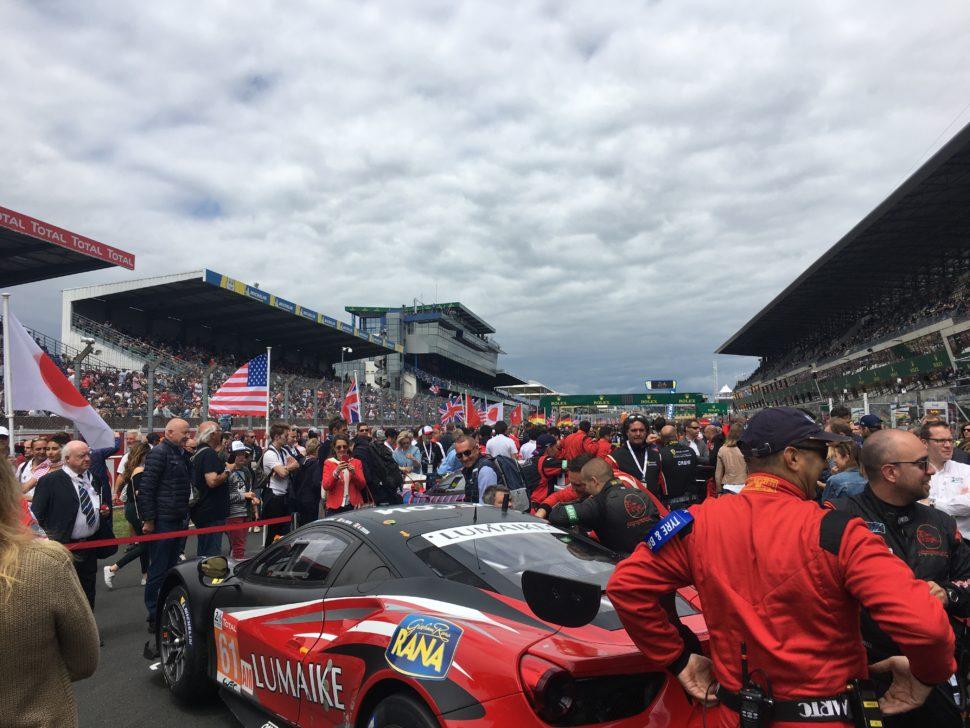 Drapeaux, pilotes, et voitures s'alignent sur la 'pitlane' quelques minutes avant le départ.