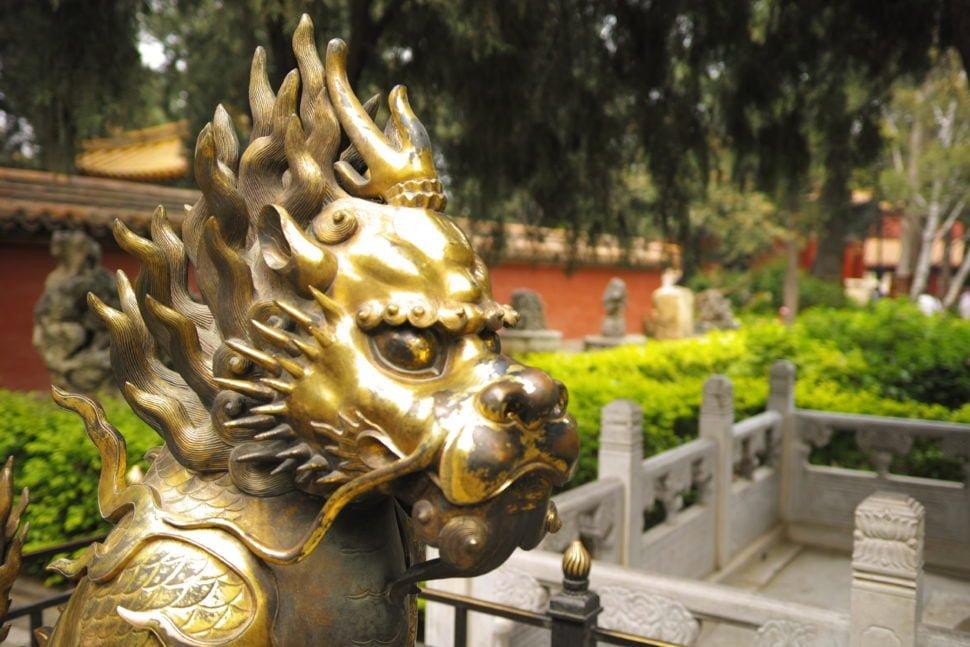 Dragon en bronze niché dans un jardin de la Cité Interdite (Beijing). Le dragon est, en Chine, la manifestation emblématique de la puissance impériale. Il symbolise les fonctions impériales