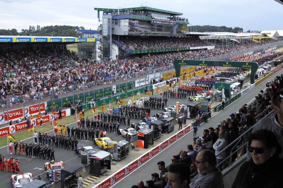 Les coureurs alignés sur la 'pitlane' des 24 heures du Mans, 87e édition, face à la foule des tribunes.