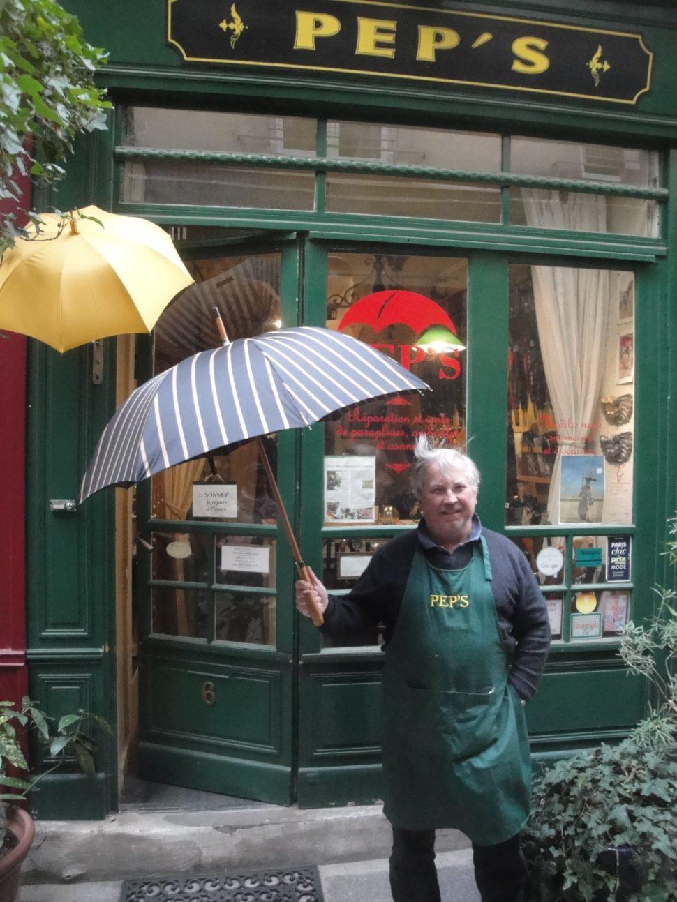Thierry Millet, devant sa boutique avec un parapluie